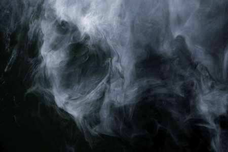 Appearance of cigarette smoke forming the shape of a skull.  Good for stop smoking ad, campaign, pamphlet, brochure or advertisement. Dry ice carbon dioxide gasses forming an image of a scary skull. Stock Photo