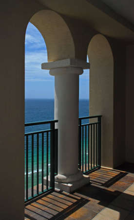 A beautiful view of the ocean and waves through the arches of a balcony. photo