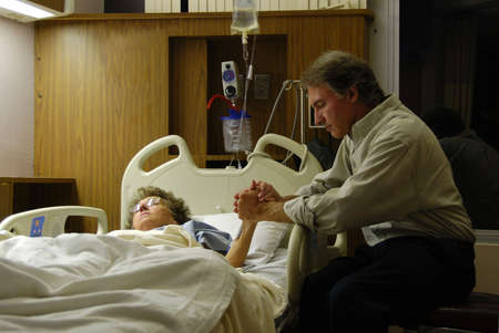 Holding the hand of a sick loved one in the hospital and praying. photo