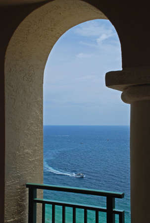 An inviting view of a boat on the ocean through an arch of a balcony. Stok Fotoğraf