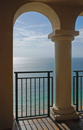 A beautiful view of the ocean through the arches of a balcony. photo