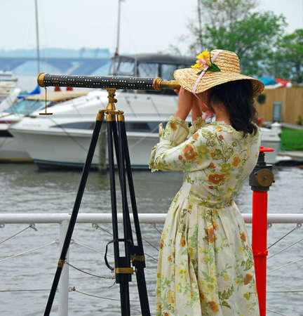 Girl looking through a telescope searching for her returning sailor.