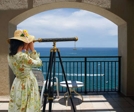 Girl in fancy dress and hat looking through telescope at the ocean from a balcony under an arch. Stok Fotoğraf