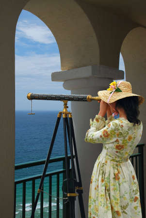 Girl in fancy dress and hat looking through telescope at the ocean from a balcony under arches. Stockfoto