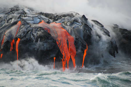 Red hot lava from Kilauea Volcano on the Big Island of Hawaii flows through lava tubes and pours like rivers into the ocean, bringing up clouds of steam and toxic gas, creating acres of lava rock and adding new land to the island. Archivio Fotografico