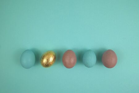 Easter egg in blue, gold and pink. Top view, arranged horizontally in a row on a blue background.