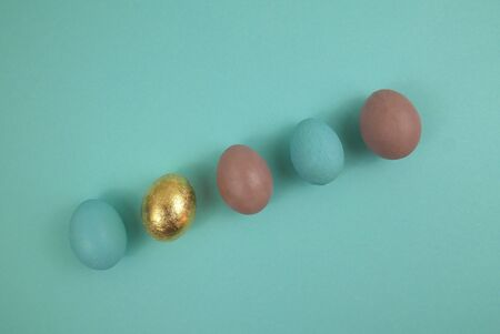 Easter egg in blue, gold and pink. Top view arranged diagonally in a row against a blue background. 스톡 콘텐츠