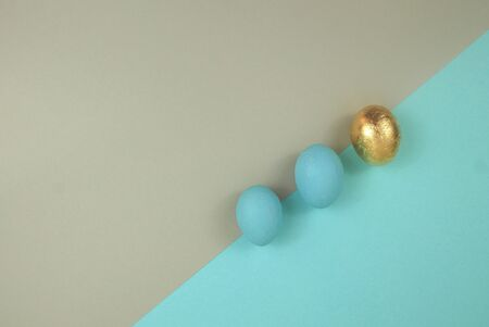 Easter egg of blue and gold color. Top view, located diagonally on a blue and beige background. 스톡 콘텐츠