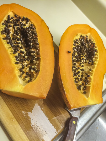 Two half papaya at the kitchen Фото со стока