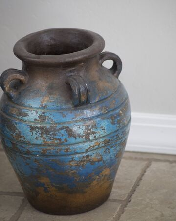 Brown and blue ceramic vase standing on the floor