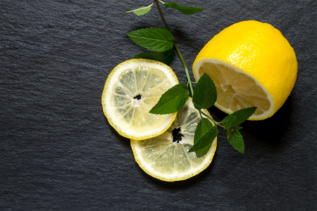 bactericidal: Organic lemon, cut into slices with a sprig of mint on a slate board