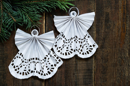 angel tree: Openwork angels in quilling techniques to spruce branch on a wooden surface for the Christmas decoration with copy space
