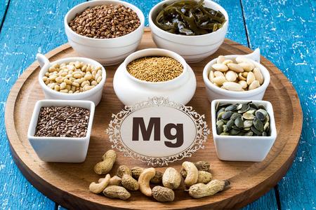 Collectie producten die magnesium boekweit, cashewnoten, pinda's, pijnboompitten, amandelen, lijnzaad en pompoen, mosterd, zeewier op een ronde snijplank en een blauwe houten achtergrond