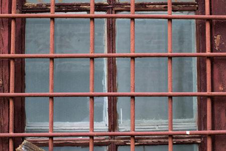 rejas de hierro: barras de hierro pintadas en la ventana de un edificio abandonado