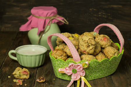 dragee: Oatmeal cookies with dragee in a basket, jug and a cup of milk on wooden background. Selective focus