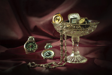 burgundy background: Old clockwork mechanical watches and chain in a glass vase on a burgundy background. Vintage style. Selective focus