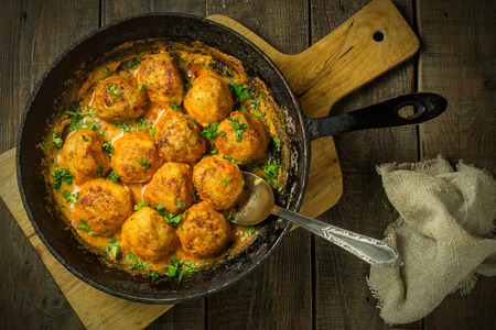 cooked pepper ball: Old cast iron pan with meatballs in sauce on a wooden background with a linen napkin.