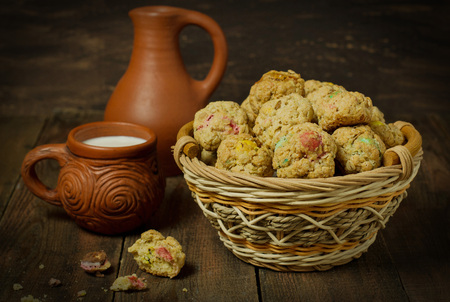 dragee: Oatmeal cookies with dragee in a basket, crock and a mug with milk on a wooden background.  Selective focus