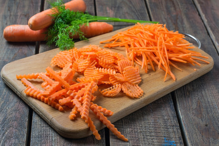 variously: Variously sliced for cooking carrots on a cutting board and parsley on a wooden background. Selective focus Stock Photo