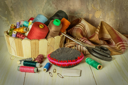 sewing supplies: Sewing supplies: thread spools in a basket, fabric, needles, chalk, scissors. Toned photo. Selective focus