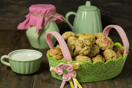 dragee: Oatmeal cookies with dragee in a basket, jug, kettle and cup with milk on a wooden background. Selective focus Stock Photo