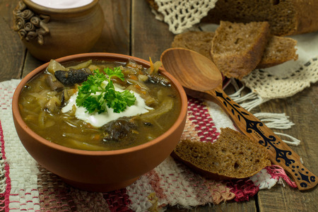 monastic: Valaam cabbage soup with mushrooms and sour cream, black bread on a wooden table. Russian traditional monastic meal. Selective focus
