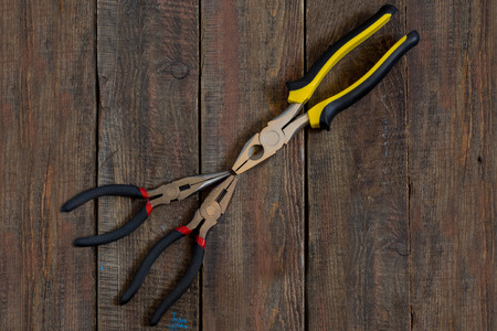 flatnose: Pliers with rubber handles, decorated with yellow and red accents on a wooden surface Stock Photo
