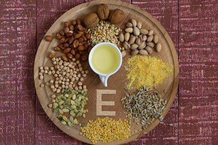 Nahrungsquellen von Vitamin E (Mais, Erdnüsse, Pistazien, Walnüsse und Pinienkernen, Sonnenblumen- und Kürbiskerne, Linsen, Erbsen, Öl) auf einem runden Brett und weißen Hintergrund