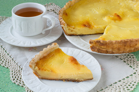 custard slice: Homemade pie with cheese and custard slice on a plate, cup of tea, a napkin with lace on a green background. Selective focus