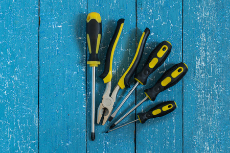 flatnose: Screwdrivers and pliers with black and yellow handles on a blue wooden background
