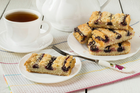 Biscuits with blueberry jam, teapot and a cup of tea on a white background