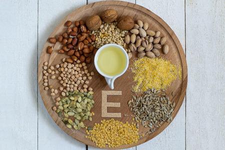 Producten op een ronde bord met een deel van vitamine E: olie, linzen, erwten, maïs, pinda's, pistachenoten, walnoten en pijnboompitten, zonnebloem en pompoenpitten