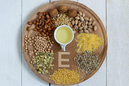 Products on a round board with a part of vitamin E: oil, lentils, peas, corn, peanuts, pistachios, walnuts and pine nuts, sunflower and pumpkin seeds