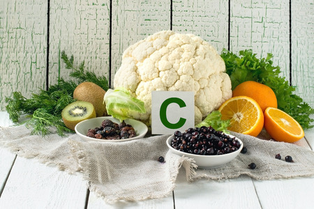 Foods containing vitamin C (cauliflower, lettuce, dill, dried rosehips, currants, oranges, kiwi) on a linen napkin