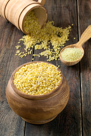 durum: Groats of durum wheat - bulgur and couscous in wooden pots, spoons on a wooden table. Selective focus Stock Photo