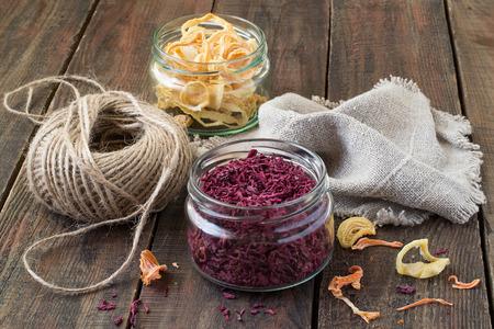 legumbres secas: Hortalizas secas en tarros (remolachas, cebollas), guita, pa�o de lino en un fondo de madera Foto de archivo