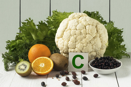 Voedingsmiddelen die rijk zijn aan vitamine C: bessen, gedroogde rozenbottels, bloemkool, sla, dille, sinaasappel, kiwi op een lichte achtergrond