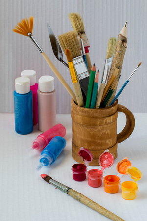 Brushes, pencils, palette knife, pen in a wooden mug and multicolored paints on a white background