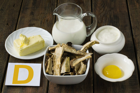 vitamins: Ingredients rich in vitamin D: butter, cream, egg yolk, sour cream, dried porcini mushrooms Stock Photo