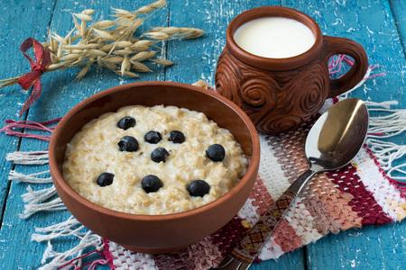 homespun: Oatmeal in a clay bowl, milk mug, homespun mat, stalks of oats on a blue wooden background