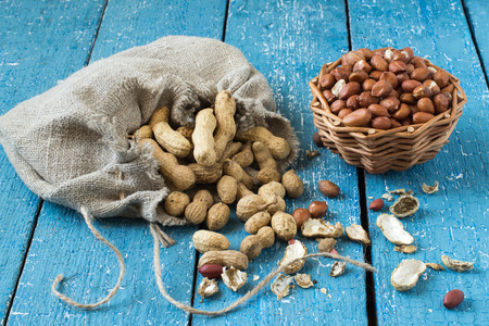 linen bag: Peanut pods in a linen bag, groundnut seeds in a basket on blue wooden table. Selective focus