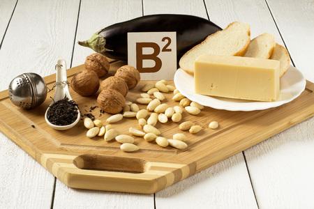 Voedingsmiddelen rijk aan vitamine B2: aubergine, kaas, wit brood, walnoten, amandelen, thee op een snijplank Stockfoto