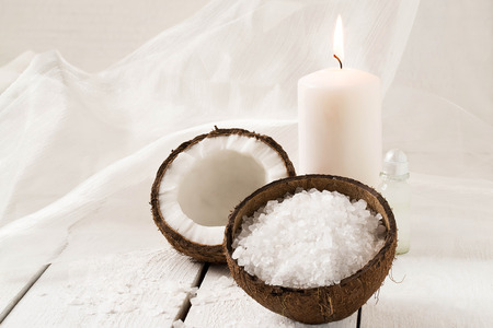 scented candle: Coconut Spa and wellness setting (coconut, sea salt, scented candle with coconut, coconut oil) on a white background