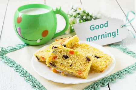 Breakfast: cake with candied fruit and milk in a green mug on a white wooden table with a wish good morning. Selective focus Stok Fotoğraf