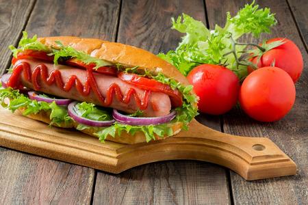 perro caliente: Perrito caliente en una tabla de cortar, los tomates y la lechuga en un fondo de madera