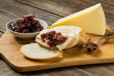 Ui jam in een schotel, wit brood en kaas op een snijplank. Selectieve aandacht.