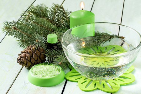 scented candle: Coniferous SPA concept: bath with sea salt and cedar oil, pine branch with cones, sea salt, oil in the bottle and scented candle on a light green painted wooden background. Selective focus