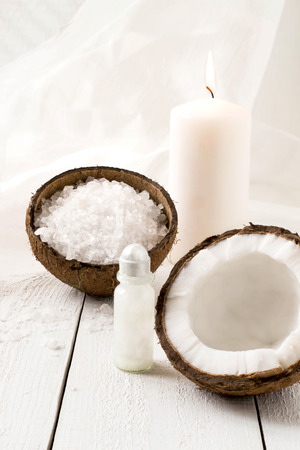 scent: Coconut Spa composition: sea salt, coconut, coconut oil and a candle with the scent of coconut on a white background. Selective focus Stock Photo
