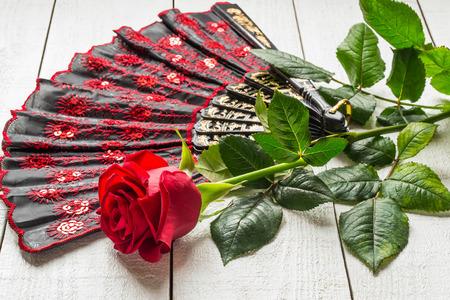 Gemusterten Fan und rot Folding Rose auf einem weißen hölzernen Hintergrund. Selektiver Fokus Standard-Bild - 47038020