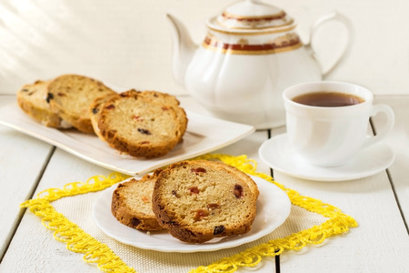plato del buen comer: Slices of cake with raisins, tea and a cup of tea on a white wooden background. Selective focus